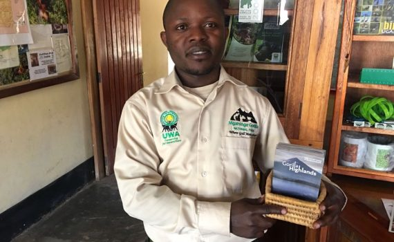 Happy of UWA Kisoro receiving Gorilla Highlands Pocket Guides 2016